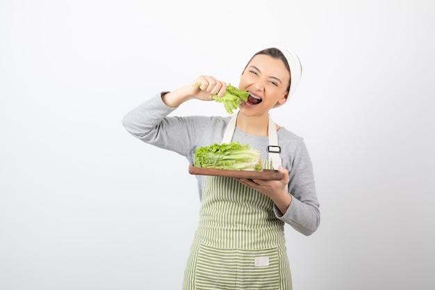 Ritratto di una donna abbastanza carina che mangia lattuga fresca