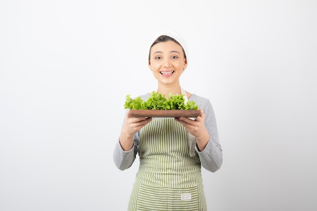 Ritratto di una donna abbastanza carina che tiene una tavola di legno con lattuga fresca