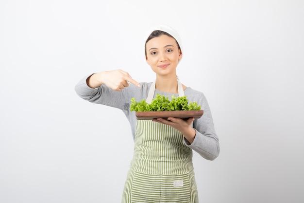 Ritratto di una donna carina che indica una tavola di legno con lattuga fresca