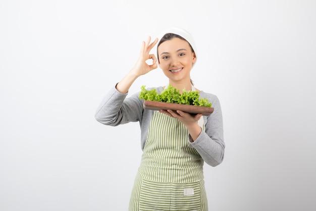 Ritratto di una donna carina con una tavola di legno di lattuga fresca che mostra un gesto ok