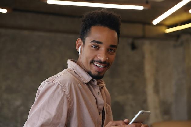Ritratto di un ragazzo barbuto dalla pelle piuttosto scura con taglio di capelli corto che guarda l'obbiettivo con un sorriso affascinante, essere di buon umore mentre posa sopra lo spazio di coworking, indossando abiti casual