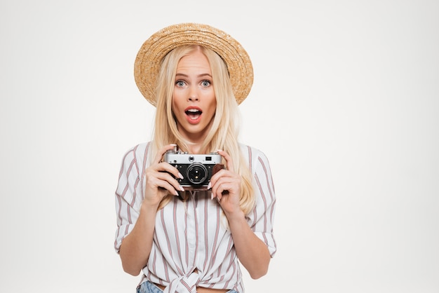 Portrait of pretty excited woman in hat holding a camera