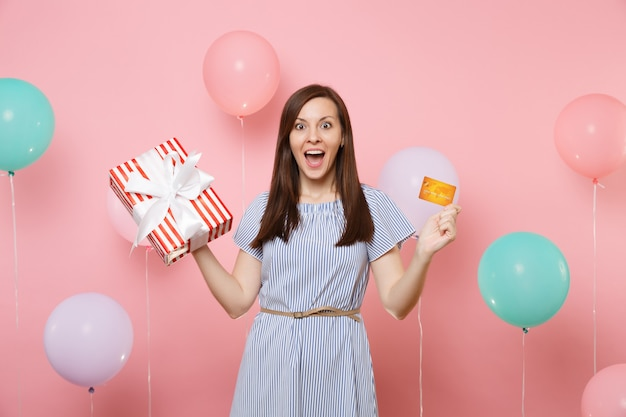 Portrait of pretty excited young woman in blue dress holding credit card and red box with gift present on pink background with colorful air balloons. birthday holiday party, people sincere emotions.