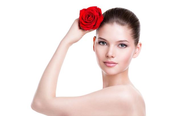 Ritratto di bel viso di bella donna con una rosa rossa - isolato su bianco.