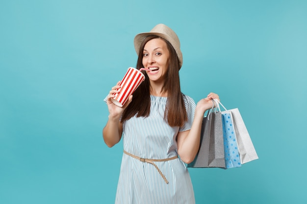 Portrait pretty fashionable smiling girl in summer dress, straw hat holding packages bags with purchases after shopping, soda water cup isolated on blue pastel background. copy space for advertisement