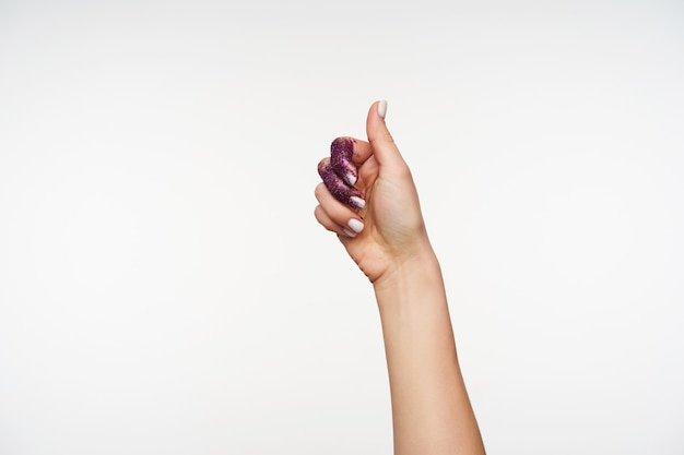 Portrait of pretty female's hand with purple sparkles on it showing raised thumb while expressing positive emotions, posing on white