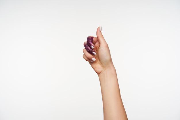Ritratto della mano della bella femmina con scintillii viola su di esso che mostra il pollice alzato mentre esprime emozioni positive, posa su bianco