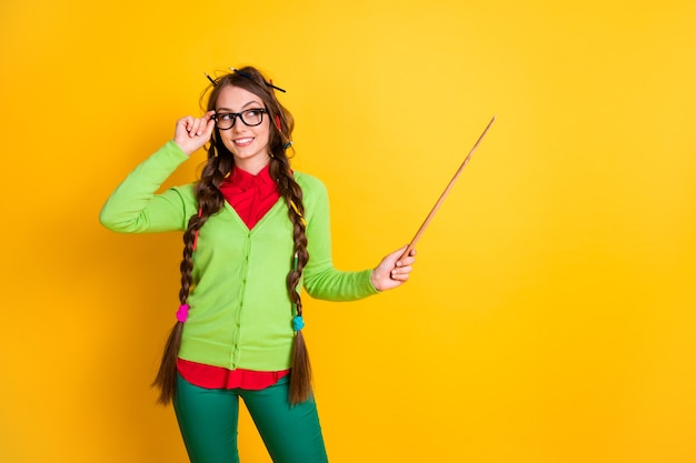 Portrait of pretty funky cheery brainy genius girl pointing copy space science teaching isolated over bright vibrant yellow color background