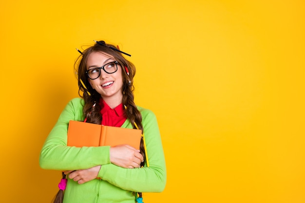 Portrait of pretty funky dreamy cheery creative intellectual girl hugging exercise book thinking copy space isolated over bright yellow color background