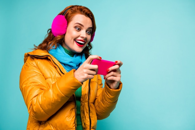Portrait of pretty funny lady hold telephone addicted video games player open mouth excited wear trendy casual ear muffs yellow overcoat scarf.