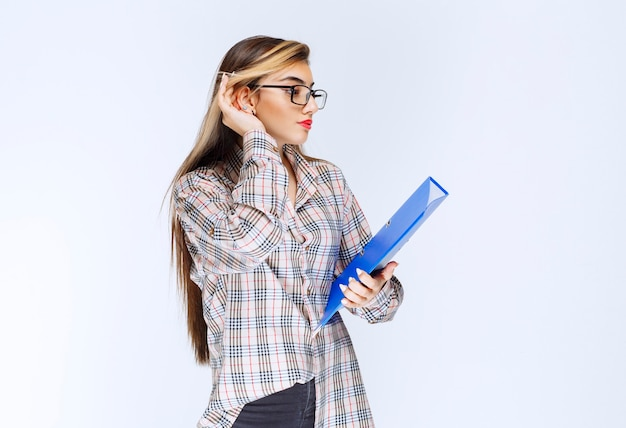Ritratto di una bella ragazza con gli occhiali in piedi una posa con una cartella.