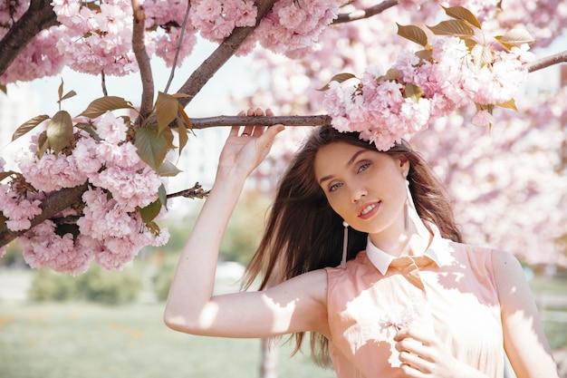 Portrait of pretty girl hiding behind branches of sakura