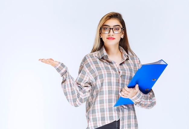 Ritratto di una bella ragazza in possesso di una cartella blu su sfondo bianco.
