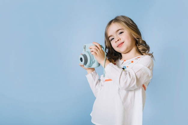 Portrait of a pretty girl holding retro instant camera in hands against blue background
