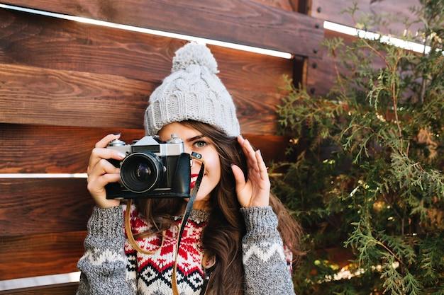 Ragazza graziosa del ritratto in cappello lavorato a maglia divertendosi a fare una foto sulla macchina fotografica su legno.