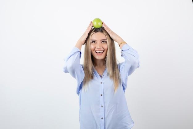 Ritratto di un modello di bella ragazza in piedi e in possesso di una mela fresca verde.