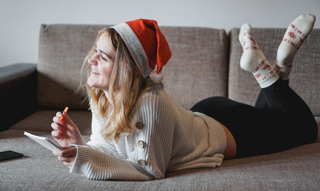 Portrait of pretty girl on the sofa at christmas writes plans for the new year