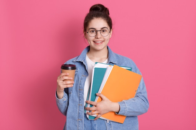Portrait of pretty girl with bun in denim jacket and white t shirt with gentle smile on pink holds folders on pink