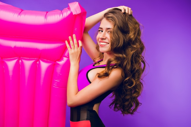 Portrait of pretty girl with long curly hair smiling to camera on purple background in studio. she wears swimsuit and holds pink air mattress.