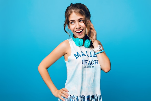 Portrait of pretty girl with long curly hair in tail talking on phone on blue background in studio. she wears white t-shirt, blue headphones on shoulders.