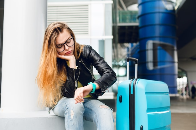 Portrait of pretty girl with long hair in glasses sitting outside in airport. she wears yellow sweater with black jacket and jeans. she leaned to the suitcase and is looking bored at watch.