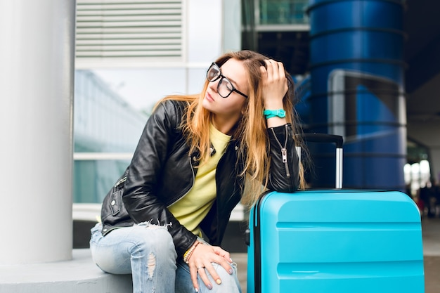 Portrait of pretty girl with long hair in glasses sitting outside in airport. she wears yellow sweater with black jacket and jeans. she leaned to the suitcase and is looking far away.