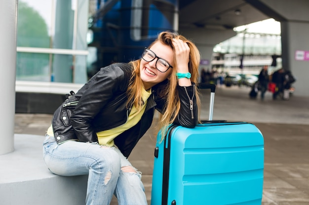 Portrait of pretty girl with long hair in glasses sitting outside in airport. she wears yellow sweater with black jacket and jeans. she leaned to the suitcase and smiling to the camera.