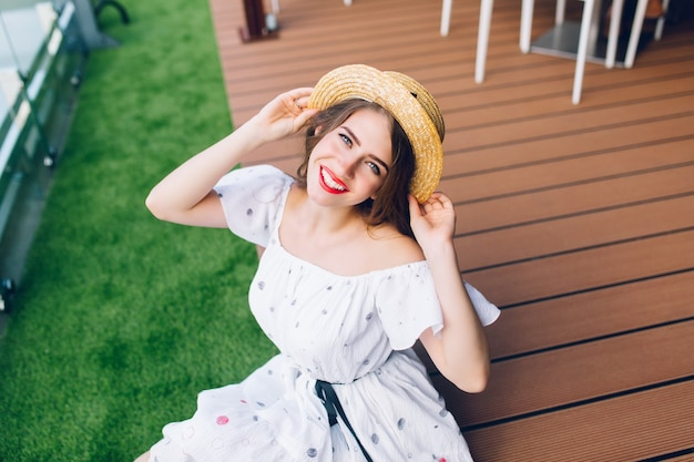 Portrait  of pretty girl with long hair in hat sitting on the wood floor outdoor. she wears a white dress with naked shoulders, red lipstick. she is smilimg to camera. view from above.