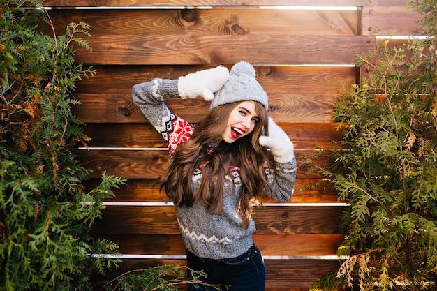 Портрет красивой девушки с длинными волосами в вязаной шапке и зимнем свитере на деревянном. она держит руки в перчатках наверху и смеется.