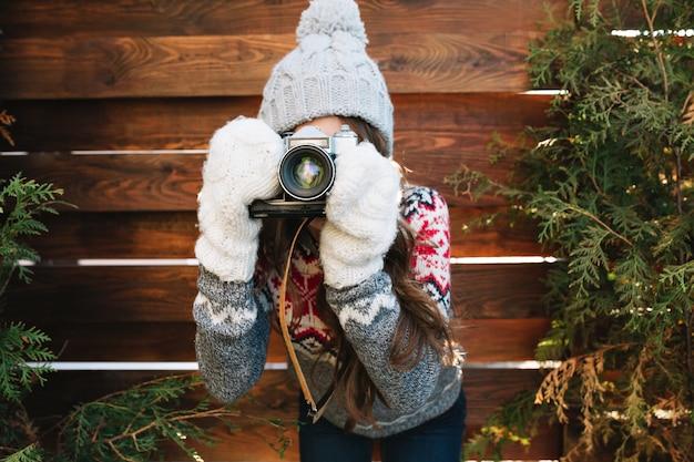 Ragazza graziosa del ritratto con capelli lunghi in cappello e guanti lavorati a maglia che fanno una foto sulla macchina fotografica su legno.
