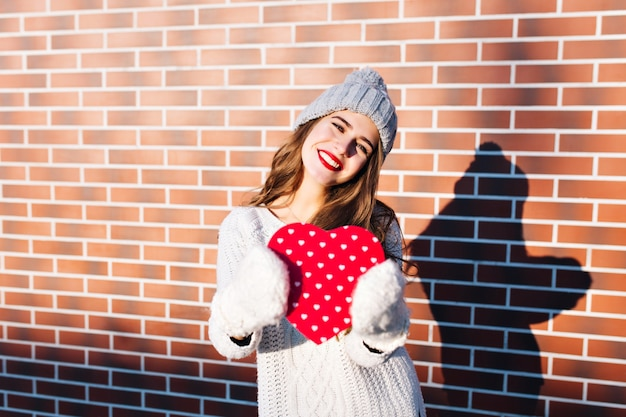 Portrait pretty girl with long hair in knitted hat, warm sweater on wall  outside. she holds red big heart in gloves, smiling .