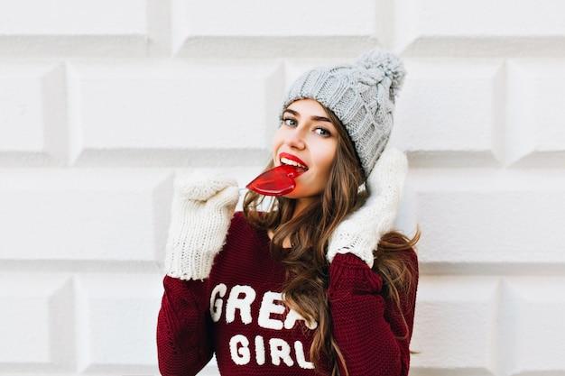 Ragazza graziosa del ritratto con capelli lunghi in maglione marsala che lecca lecca-lecca cuore rosso sul muro grigio. indossa guanti bianchi, sorridendo.
