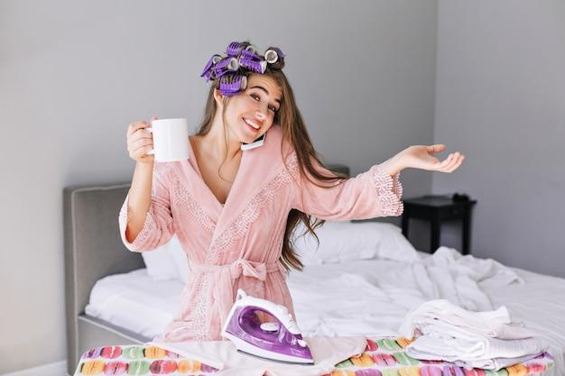 Ragazza graziosa del ritratto con capelli lunghi in accappatoio rosa e bigodino sulla testa a stirare i vestiti a casa. lei parla al telefono, tiene la tazza, sorridendo.