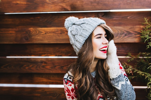 Portrait pretty girl with long hair and red lips  in knitted hat and warm gloves on wooden . she is smiling to side.