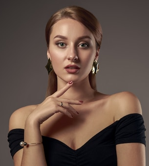 Portrait of pretty girl with natural make up wearing black off shoulders dress and touching face
