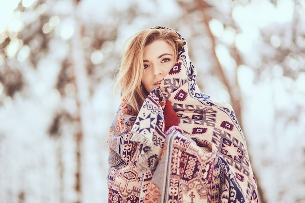 Portrait of pretty girl, wrapping in scarf on a winter park
