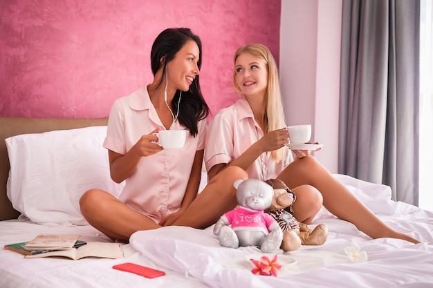 Portrait of pretty girls in pink pyjamas having mugs with coffee in hands and looking to each other while sitting on the bed