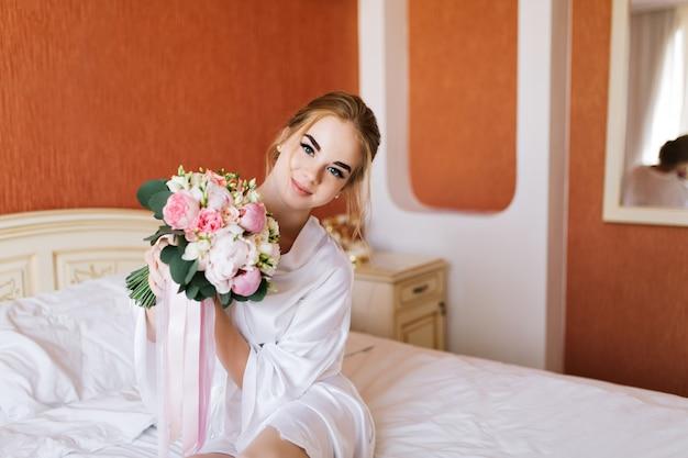 朝ベッドの上の花と白いバスローブの肖像画かなり幸せな花嫁。