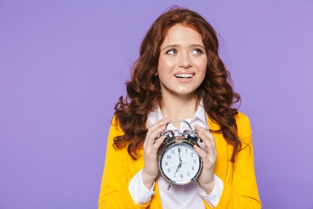 Portrait of a pretty happy young redheaded woman standing over violet, showing alarm clock