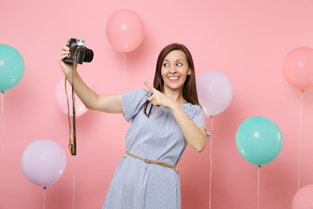 Portrait of pretty happy young woman in blue dress doing selfie pointing index finger on retro vintage photo camera on pastel pink background with colorful air balloon. birthday holiday party concept.
