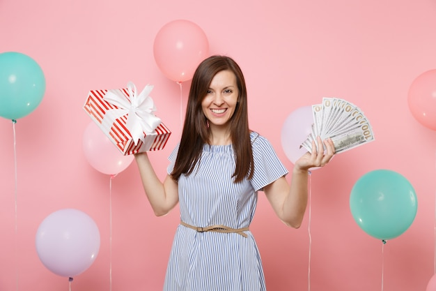 Portrait of pretty happy young woman in blue dress holding bundle lots of dollars cash money and red box with gift present on pink background with colorful air balloon. birthday holiday party concept.