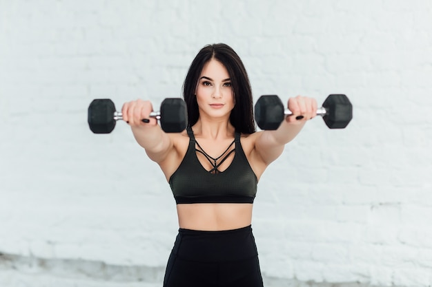 Portrait of pretty indian woman exercising with dumbbells.