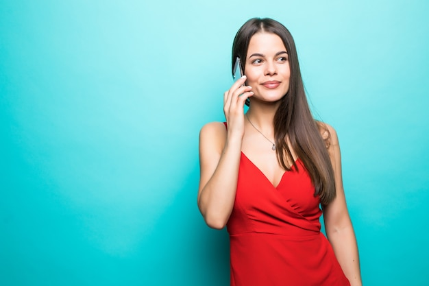 Ritratto di una ragazza abbastanza gioiosa in vestito rosso che parla sul telefono cellulare isolato sopra la parete blu