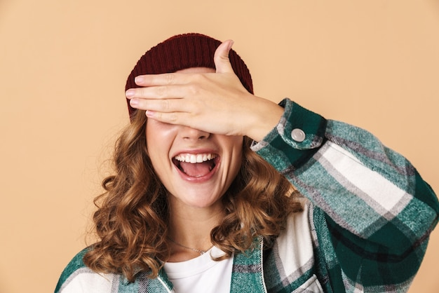 Portrait of pretty joyful woman in knit hat laughing and covering her eyes isolated over beige wall