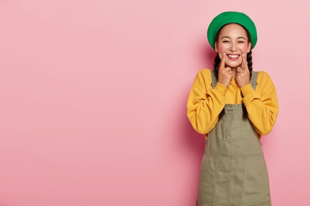 Portrait of pretty joyous girl with rouge cheeks, keeps index fingers near corner of lips, smiles sincerely, wears green beret, yellow sweatshirt