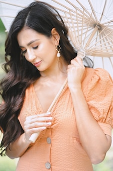 Portrait of pretty lady at nature holding umbrella in orange dress during daytime.