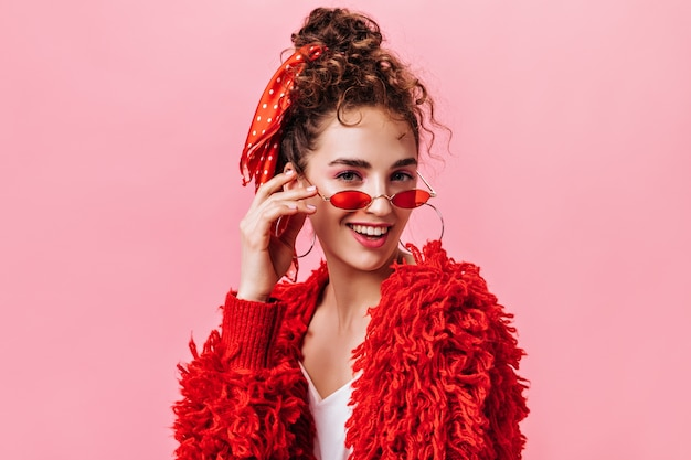 Portrait of pretty lady in red warm jacket and stylish eyeglasses