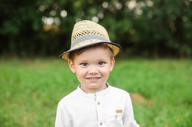 Portrait of pretty little boy in stylish clothes walks outside