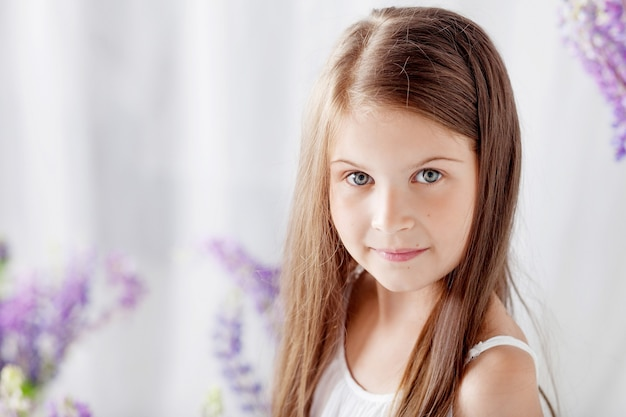 Portrait of pretty little emotion girl among violet flowers.clouse up picture of beautiful smiling girl