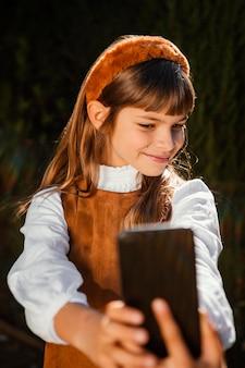 Portrait of pretty little girl taking a selfie